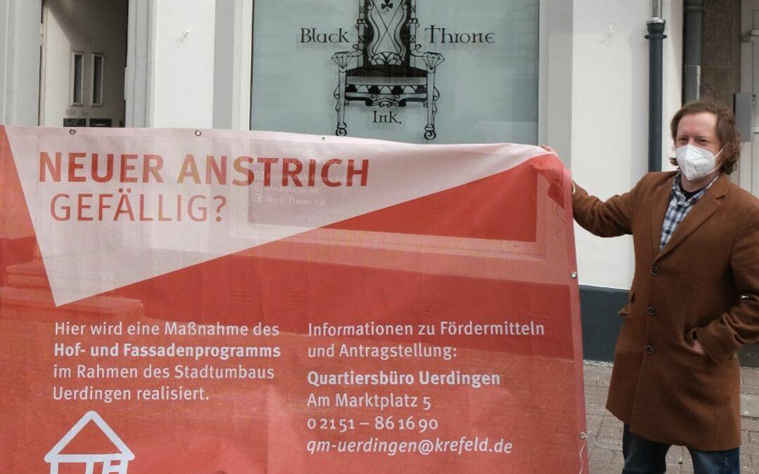 Der Eigentümer Christopher Dahlen steht vor seinem Objekt in der Oberstraße 43, dessen Fassade gerade mit öffentlichen Fördermitteln saniert worden ist. In der Hand hält er ein Transparent zur Bewerbung des Förderprogramms mit dem Slogan Neuer Anstrich gefällig?